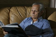 An older man examines a photo in an album Stock Images