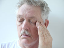 Older man with eye fatigue Royalty Free Stock Photos