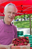 Older man at Farmer's Market. A senior man displays a box of fresh strawberries he's just purchased at an outdoor Farmer's Market Stock Photo
