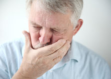 Older man feels nausea. Senior man holds his hand to his mouth while feeling nauseous Royalty Free Stock Images