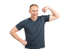 Older man flexing muscles and smiling. Royalty Free Stock Image