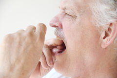 Older man flossing teeth profile view Royalty Free Stock Photo