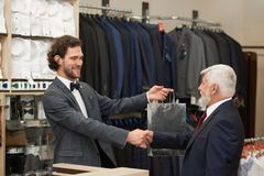 Older man giving hand to smiling to salesman. stock photography