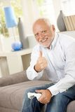 Older man giving thumb up with computer game. Older man sitting on couch giving thumb up while playing computer game, looking at camera, smiling Royalty Free Stock Photos