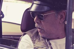 Older man with glasses driving a car Stock Images