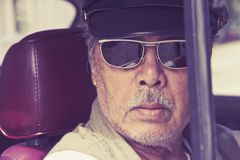 Older man with glasses driving a car Stock Image