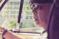 Older man with glasses driving a car Stock Photo