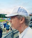 Older man with goatee, curly grey hair and white cap at baseball stock photo