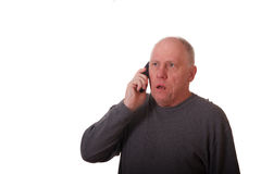 Older Man in Gray Shirt Getting Bad News on Phone Stock Photo