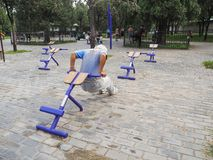Older man with grey hair working out on public equipment royalty free stock image