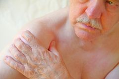 Senior man grips his sore shoulder stock images