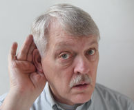 Older man is hard of hearing. Senior male cups his ear in order to hear better Royalty Free Stock Image