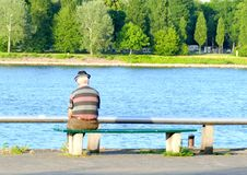 Older man sitting on a bench royalty free stock images
