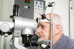 Older man having eye examination. An older man taking an eye test examination at an opticians clinic Royalty Free Stock Images