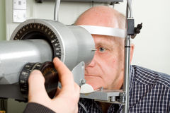 Older man having eye examination. An older man taking an eye test examination at an opticians clinic Stock Photography