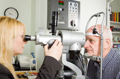 Older man having eye examination. An older man taking an eye test examination at an opticians clinic Royalty Free Stock Photography