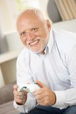 Older man having fun with computer game Stock Photography