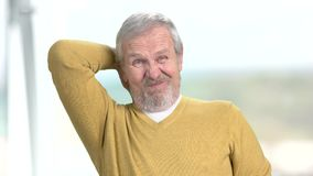 Older man having terrible neck pain. Stressed senior man suffering from strong ache in neck, blurred background stock video