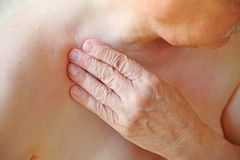 Senior touches his aching shoulder closeup stock image