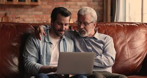Older man his millennial son sit on couch with laptop
