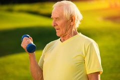 Older man holding a dumbbell. royalty free stock photography