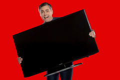 Older man holding plasma screen. Stock Photo