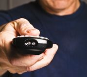 Older man holding tv remote control Royalty Free Stock Photos