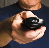 Older man holding tv remote control Stock Photography