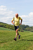 Older man jogging running on meadow royalty free stock image