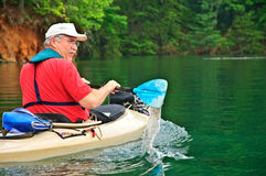Older Man Kayaking. Close up of a man kayaking on a beautiful, quiet lake, he's a babyboomer aged, active person. This was on Lake Jocassee in South Carolina Stock Image
