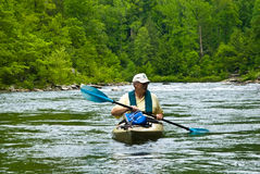 Older Man Kayaking/River Rapids. A babyboomer aged man in a kayak on a peaceful spot in the river.  This was taken from my kayak so that the perspective is at Stock Photo