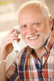 Older man on landline phone call. Portrait of older man on landline phone call, smiling happily at camera Royalty Free Stock Image