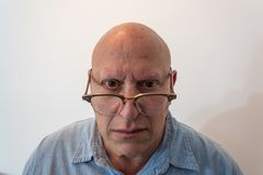 Older man looking over horn rimmed glasses, bald, alopecia, chemotherapy, cancer,  on white Stock Photography