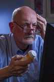 Older man looks confused while refilling prescription online, vertical Stock Photos