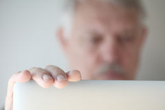 Older man looks at laptop with copy space Stock Images