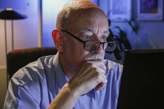 Older man looks serious as he reads off computer, horizontal Royalty Free Stock Photos