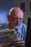 Older man looks upset as he pays bills online, vertical Stock Images
