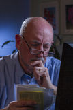 Older man looks worried as he pays bills online, vertical Stock Photo