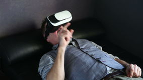 Older man lying on couch with virtual reality glasses stock footage