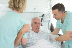 Older man lying in hospital bed with nurses helping him stock image