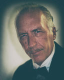 Older man with mustache vintage color. Portrait of an older white man in formal dress tuxedo, slicked back hair and pencil mustache, looking at viewer with old Stock Images