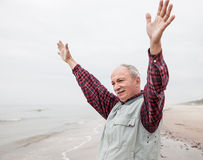 Older man with outstretched arms the coast Stock Images