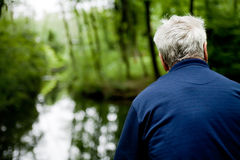 Older man overlooking a stream Royalty Free Stock Photography