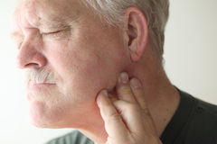 Older man with painful jaw. Senior man frowns as he touches his sore jaw royalty free stock image