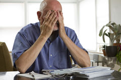 Older man paying bills. Man reacting to paying bills Royalty Free Stock Photo