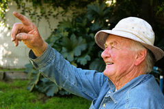 Older Man Pointing. To something in his yard Royalty Free Stock Photo