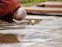 An older man praying to Buddha Stock Photo