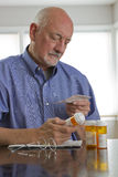Older man with prescription medications, vertical Royalty Free Stock Photos