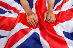 The older man put his hands on the UK flag. The older man put his hands on the UK flag Royalty Free Stock Photography