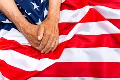 The older man put his hands on the us flag. The concept of carin. G for pensioners Royalty Free Stock Photo